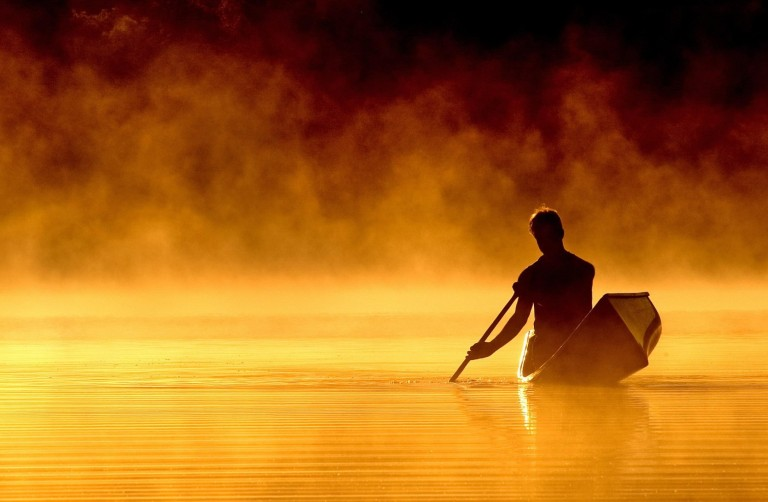 photo of man in canoe on misty lake, finding purpose