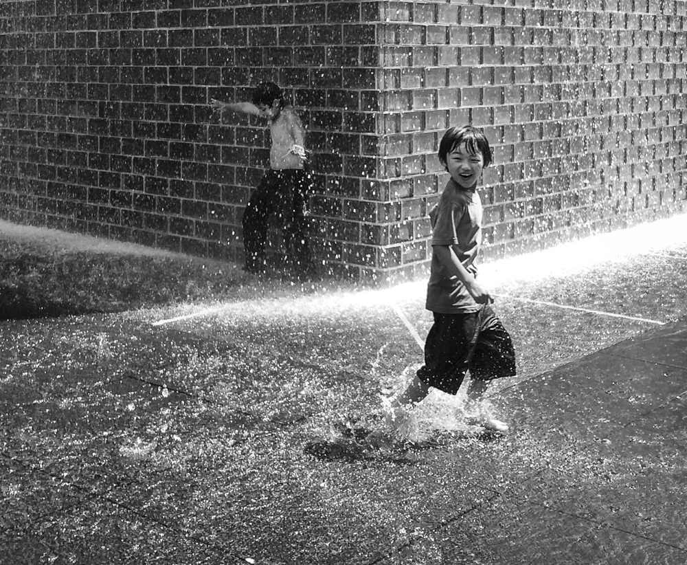 Picture of children playing barefoot in the rain