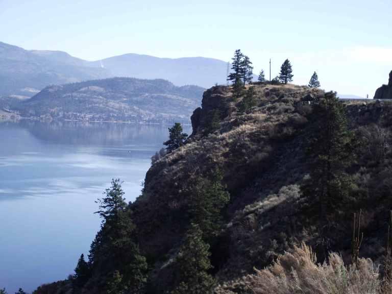 Photograph of beautiful mountains and pine-dotted terrain of Okanagan Lake, British Columbia