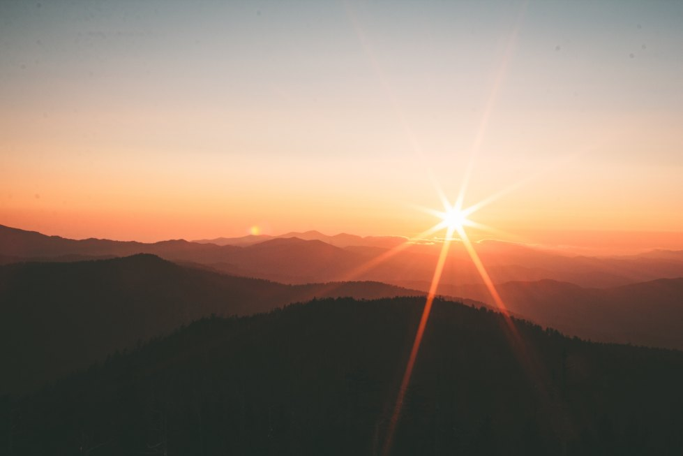 Beautiful, ethereal visual of a gleaming sun over mountains